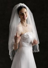 This two-tier veil features a beautifully beaded scallop edge, beaded flowers and sequins. The fingertip length measures approximately 40 inches long. Wire comb. Available in White or Ivory. Imported.