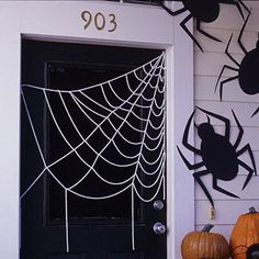 Halloween crafts: Hang gigantic crawling spiders on the outside of your home this year with black paper.