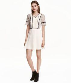 Gebroken wit. Een korte jurk van chiffon en kant met strikbandjes bij de…