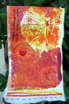 "Buddhist Prayer Flag. Cut background fabric to 5""x11"". Folding a short end over by 3"" & sew down with decorative stitching – leave a tunnel space for string for hanging. Embellish a prayer theme with paper, painting, stitch, embroidery, buttons, etc. Include the date, and add a word to the surface of the flag. Photograph the completed flag & write about the process & the 'prayer'."