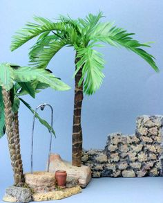 Model stone wall made from styrofoam bead board shown beside a palm tree with a base of florist's foam, both designed to fit with pieces from a Department 56 Little Town of Bethlehem Village.