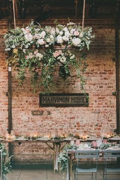 Sarah and Robin of GATHER Events used bountiful hanging blooms to lend a soft, romantic vibe to this lofty industrial space. Via GATHER Events