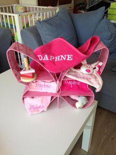 Leuke kraammand. Vlinder van ijzer gevuld met leuke producten voor een baby zoals een slabber, spuugdoek, knuffeltje, badcape en speeltjes.