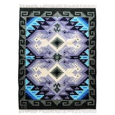 "With precise geometric shapes, Eliazar Ochoa invokes Andean ancestors. Blue, grey and lilac depict Inca tocapu signs and symbols, which they used as an alphabet. This intricate wool rug is woven by hand of virgin wool and finished with luscious fringe.   Titled ""Reflejos de mar y cielo"" in Span..."