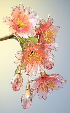 """These beautiful flowers may look like they are made of glass, but they are actually made from wire and liquid synthetic resin. Japanese Kanzashi (hair ornament) artist Sakae is the Maker behind this craft which she calls """"dip flower."""" It involves bending Nylon Flowers, Wire Flowers, Fabric Flowers, Paper Flowers, Flowers In Resin, Plastic Bottle Flowers, Plastic Bottle Crafts, Plastic Resin, Plastic Bottles"""