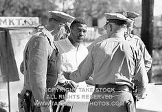 TAKE STOCK photo. Willie James Shaw, a SNCC worker, being arrested in Belzoni for encouraging local blacks to vote in a COFO 'Freedom Election'. Police said Shaw was parked too close to a fire hydrant.
