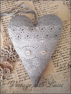 diluted black silk dye to turn white fabrics and laces into shades of gray...the lace heart front consists of five different eyelet laces and is embellished with gray beads and coffee dyed linen buttons.