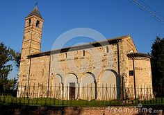 Photo taken at the small and ancient church Pozzoveggiani that is in the province of Padua in Veneto (Italy). In the photo taken at the south side you can see the whole side of the church and its belfry exposed to the morning sun. Complete the setting of the church brick color green of the grass and of course the deep blue sky.