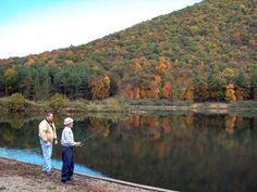 Anglers fish in the reflective water of the lake with a mountain in the background at Sinnemahoning State Park, Pennsylvania.