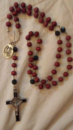From the Spiritual Warfare collection: the rosewood Benedictine Rosary. Rosewood Hail Mary beads that let the faint scent of roses waft through your fingers as you pray. Black faceted Our Father beads. St.  Benedict centerpiece and Crucifix. St. Michael medal with Guardian Angel on the other side of it for extra protection. Great gift!
