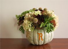 Great centerpiece for the fall.  They used a vegetable peeler to monogram the pumpkin.