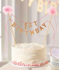 Top the 1st Birthday Cake with this gorgeous pink topper. Birthday cake topper reads '1st Birthday' in glitter felt strung between two pom-pom topped wooden dowel posts. Fits in cakes of all sizes and