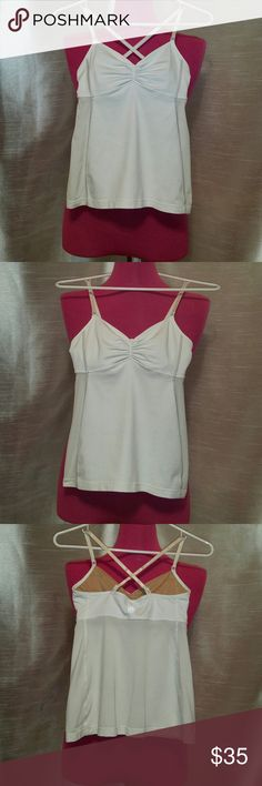 Lululemon Tank w/ Mesh Back & Built in Bra You'll love this Lululemon white tank! It is white in the front & white(ish) mesh on sides & back. There are colored stripes, down both sides, to give it a POP of color! BEST THING, imo, is the mesh-like/BREATHABLE material, which makes up 75% of this tank! (Why be overheated?) It has adjustable straps, to tighten, loosen, criss-cross, or keep it simple. (The straps match the mesh color, so they're not bright white) Has a built-in bra, no inserts…