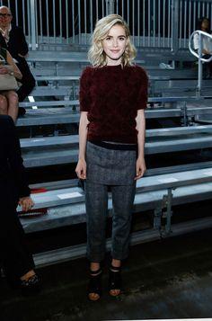 Kiernan Shipka wears a 3.1 Phillip Lim burgundy sweater, wool pants, and black ankle-strap heels