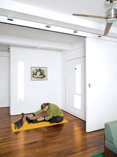 """Robert Garneau's Transformer Loft is just 550 sf and includes this 8' wide bedroom. Where? A hydraulic Murphy bed folds down with fingertips. A 500-pound track-mounted sliding wall that both separates their office/kitchen from the bedroom relies on ball bearings so smooth it makes little noise when it moves, despite being heavy enough to act as a real wall. It's solid, 2"""" thick construction with a layer of acoustic drywall and plywood, engineered to hang from a beam."""