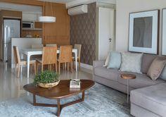 Acabamentos na cor branca e em madeira freijó definem esta cozinha do apartamento em São Paulo (SP) projetado por Ana Yoshida. Quando a porta de correr (Marcenaria Edlucas) está aberta, o cômodo se integra com o living, permitindo a interação dos moradores com as visitas