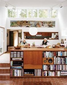 Peter Cohen and his wife, Sally, sit in the connected dining-living room, which is a focal point of their Maine home. Lighted in part by high, remote-controlled clerestory windows, the low shelving unit that divides the two spaces incorporates audio components as well. Photo by: Mark Mahaney - Dwell | At Home in the Modern World: Modern Design & Architecture