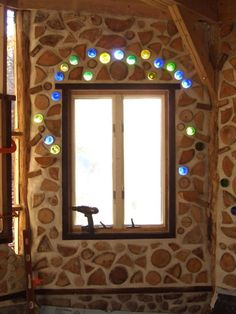 cordwood constructioncordwood house Glass bottles frame the window. Cordwood walls on top of a stone foundation