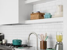 """Classic white subway tiles, outlined in gray grout, go from countertop to ceiling, making the room feel bigger. They also turn most of the kitchen's walls into one giant easy-to-clean backsplash. """"It's low-maintenance but also has a clean, industrial look,"""" says Danielle."""