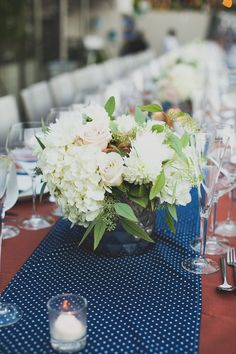 white centerpiece with dotted table runner // photo by Mr. Haack // http://ruffledblog.com/metallic-orange-county-wedding/