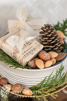 Small presents wrapped in sheet music with simple white bows, pine cones, greenery and nuts.