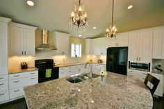 White Cabinetry, Granite Counter Tops, kitchen island, Stove hood vent, island sink