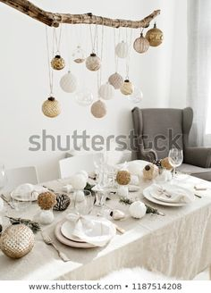 Festive living room decorated for Christmas and New Year with stylish table set for four person and vintage Christmas decoration hanging above it.