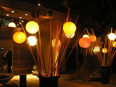 -Lanterns with battery-operated string lights for illumination   -Situated at entrances, &/or  -Spread out in a line across width of room to visually tighten it, &/or  -On either side of DJ, &/or  -Rather than this large, picture small illuminated lanterns on bamboo or painted dowels on the tables.  -Wouldn't want all, but maybe 1 or 2 (entrances & DJ, or to tighten room & DJ)