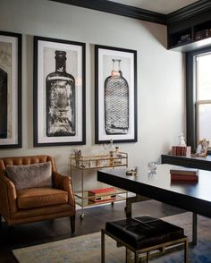A glass-and-gold bar cart, brown leather armchair and oversized artwork of glass bottles give Mad Men-esque flair to this home office.