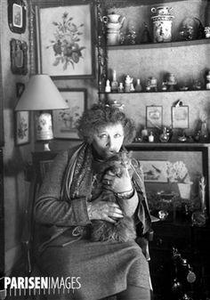 Colette (1873-1954), écrivain français et son chat, dans son appartement du Palais-Royal. Paris (Ier arr.), 1935.