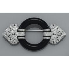 AN ONYX AND DIAMOND BROOCH The onyx sphere flanked to either side by a pierced circular-cut diamond set motif. Art Deco or Art Deco style