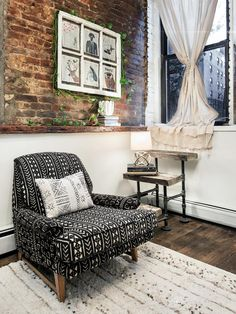 The exposed brick above the sitting room in this apartment gives the space character. Even though the space is small, designers have incorporated a large chair and a small side table. The ledge that frames the exposed brick also provides extra space for decorating and setting a cup of tea.