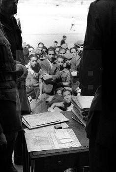 Madrid, 27-6-1941.- El Teniente Coronel Joaquín López Tierda, de las milicias de falange, en la oficina de reclutamiento de voluntarios de la División Azul situada en la Ciudad Universitaria. En la foto, un grupo de jóvenes junto a la mesa de reclutamiento. EFE.