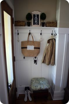 Mudroom entryway with board and batten wall, hooks, shelf ledge