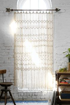 exposed brick accent wall and bohemian curtains. Interior design inspiration.