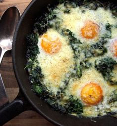 Recipe for Eggs Poached in Spinach - The eggs are poached in deliciously buttery garlic spinach, and topped with a crunchy parmesan crust.