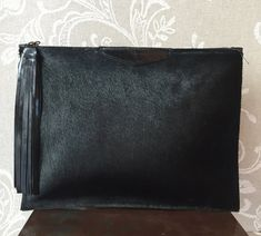 This black cowhide leather clutch is a perfect accessory to bring an edgy twist to your outfit. Also you can use this clutch as a luxury Ipad case. Hand made in genuine cowhide and leather. Inside: fabric lining, w/one zipped pocket. Outside: zipper accross the top.  Height: 9 1/2( 25 cm) / Width: 13 (34 cm) This clutch is made to order, please allow 10 working days for delivery. Shipping through private courier only 4-5 business days to reach any destination   See more clutche...
