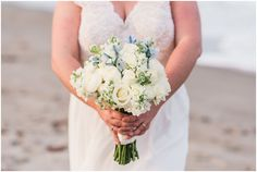 Bride holding bouquet of white roses on beach during Cocoa Beach Weddding