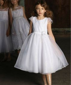 The Eva dress, made of sequined organza.A graceful tea length gown, the Eva will add a touch of elegance to any special occasion. Eva is white organza dress, with a hidden rear zipper and is fully lined. This delicate dress will sparkle for your next event, whether it be a wedding, baptism, first communion or special picnic.
