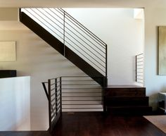 The thin black lines of the blackened steel railing against the white wall make for a delicate, minimalist and sculptural stair here.