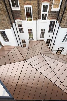 A faceted roof made from a shimmering copper-bronze alloy covers this office extension by British firm Emrys Architects to a pair of Georgian townhouses in London.