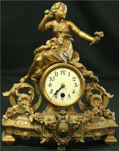 Gilded metal French Rococo clock dating to 1890. A pretty lady brushes her hair while admiring a bunch of flowers on the (still working) antique clock.  EuroLuxAntiques.com