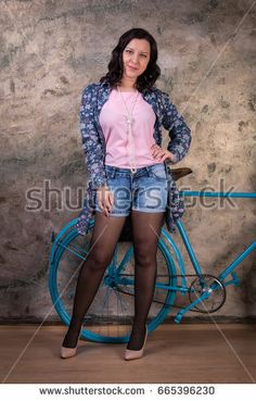 Attractive brunette woman in denim shorts and black pantyhose with bicycle. Studio portrait of a sexy girl. #665396230