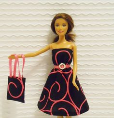 """Barbie Clothes Barbie Dress in Black with Hot Pink by BarbiesRUs, $4.25, Barbie dress is stunning in a modern retro look with a hot pink swirl design on black. Barbie's dress has a hot pink satin ribbon sewn on for a belt with a pearl belt buckle which adds elegance & Barbie dress has elastic at the waist for a nice fit & velcro closures in the back makes for easy on/off.     Barbie's matching purse is 4"""" high with handles and 2 1/2"""" without the handles and 2"""" wide with hot pink ribbon to match"""
