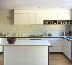 Geometric tiled splashback, white kitchen, timber details Cantilever interiors Melbourne
