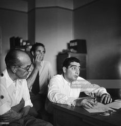 Robert Capa  chairs a meeting of the Magnum photographic co-operative, Paris, circa 1947. Swiss photographer Werner Bischof , can be seen in the background, centre.