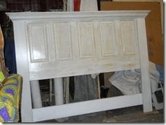 Headboard made out of an old Door.... Thinking we might do this :)