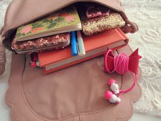 """In my little purse: my new darling daily planner from Frankie Magazine, the sweetest lipstick//coin purse that my Ma made me, my """"thoughts//notes"""" journal, headphones & iPod, and my pink sequins wallet."""