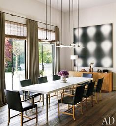 A dining area featuring pendant lighting and a bold piece of art | archdigest.com