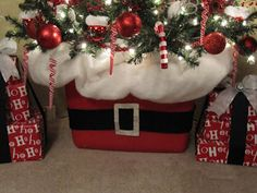 """The box I used for the base is the Rubbermaid box I store the ornaments in for this tree. (Here's a side tip...I use red boxes for Christmas, brown for fall, orange for Halloween and blue for Easter. Helps to find things in the attic faster)   Last year for the base, I used a big galvanized tub. The metal """"trunk"""" of this tree is very long and looks un-natural, so I always like to disguise it some how.  I just plunk the tree in there, packed it with newspaper and covered it with a big piece o"""